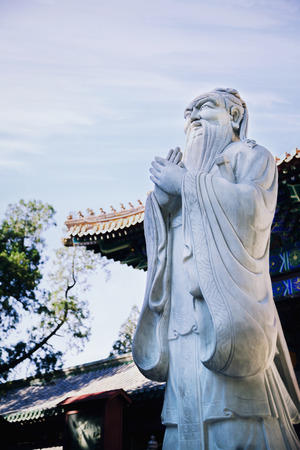 Stone statue of Confucius, traditional pagoda in the background