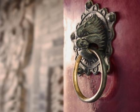 door knocker: Close-up of ornate gold door knocker on red door Stock Photo