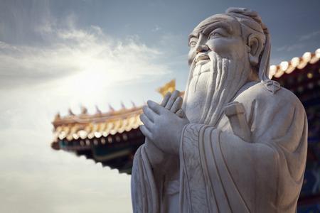Close-up der Steinstatue von Konfuzius, Pagodendach im Hintergrund