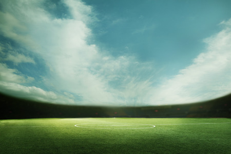 Digital composite of soccer field and blue sky Stock Photo