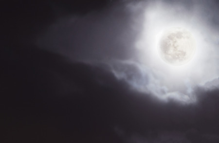Full moon in night sky with clouds.