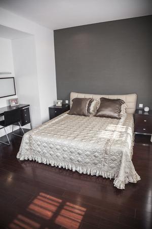bedspread: Bright, modern bedroom with beige bedspread. LANG_EVOIMAGES