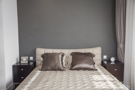 bedspread: Bright, modern bedroom with beige bedspread. LANG_EVOIMAGES