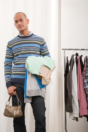 coathangers: Man holding clothes and handbag