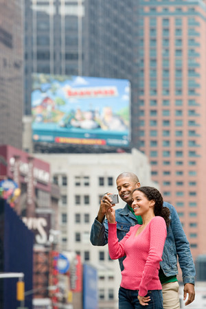 african american male: Couple using digital camera