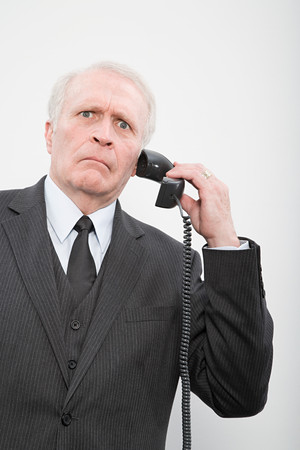grown ups: A confused businessman using a telephone