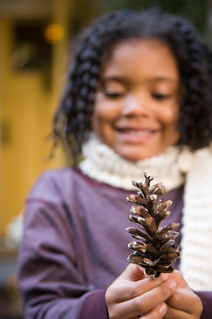 afro caribbean ethnicity: Girl with a pine cone Stock Photo