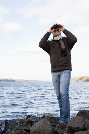 30 to 40 year olds: A man using binoculars