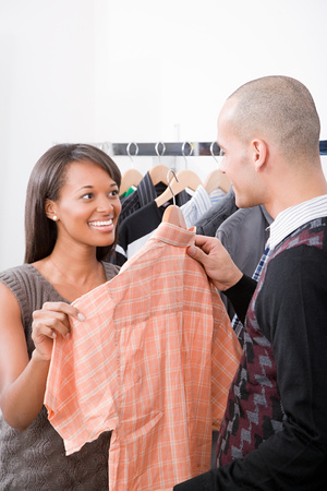 coathangers: Man and woman in clothes shop Stock Photo