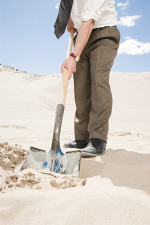stood up: Man digging in desert Stock Photo