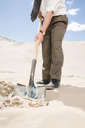 hold ups: Man digging in desert Stock Photo