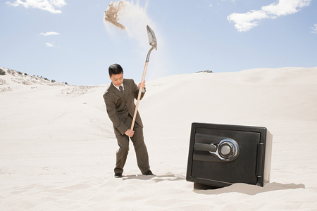 30 to 40 year olds: Man digging by safe in desert Stock Photo