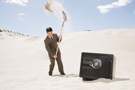 Man digging by safe in desert Zdjęcie Seryjne