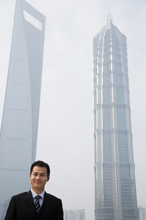 35 to 40 year olds: Chinese businessman near skyscrapers Stock Photo