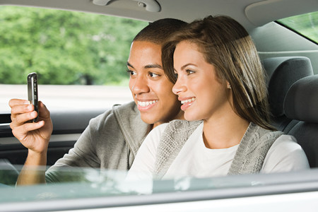 afro caribbean ethnicity: Young couple using a cellular phone in car Stock Photo