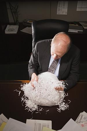 officeworker: Mature businessman playing with paper shreddings Stock Photo