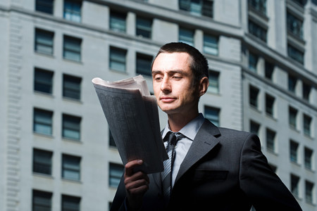 30 to 40 year old: Businessman reading a newspaper Stock Photo