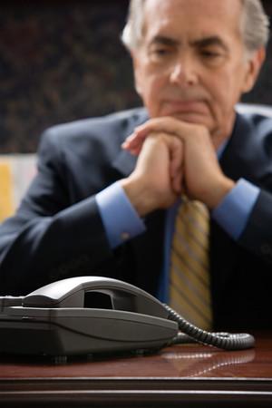 ponderous: Pensive businessman with telephone Stock Photo