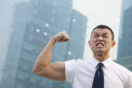 Portrait of young angry businessman flexing muscles photo