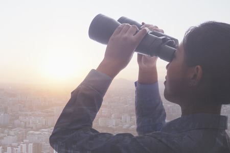 bigger picture: Double exposure of young businesswoman holding binoculars over cityscape of Beijing