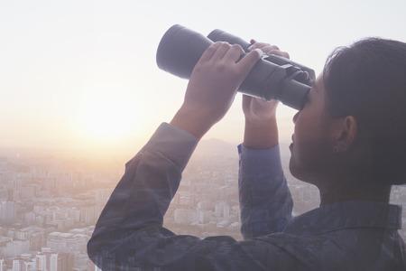 multiple ethnicities: Double exposure of young businesswoman holding binoculars over cityscape of Beijing
