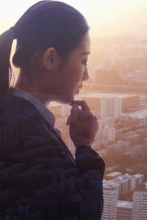 the bigger picture: Profile of young businesswoman contemplating, double exposure of cityscape, Beijing