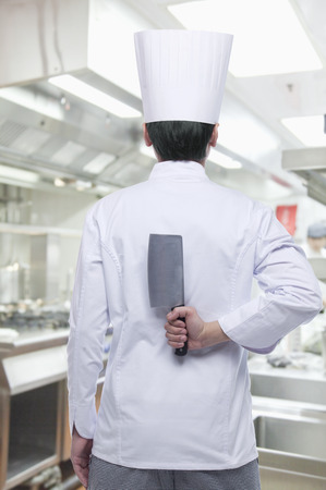 Rear View of Chef with Knife Behind his Back photo