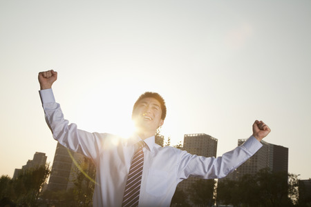 Young businessman with fists in the air celebrating Banco de Imagens