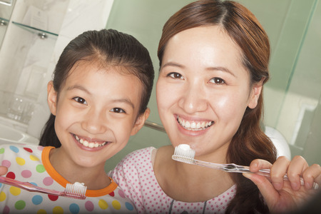 Mother and Daughter Brushing Teeth Together photo