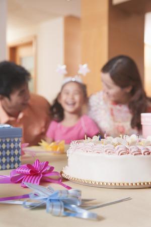 Family Celebrating Girls Birthday - Focus On Birthday Cake photo
