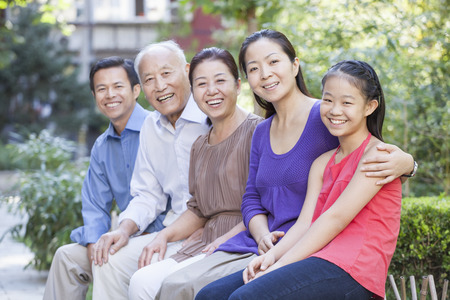 three generation: Three Generation Family Sitting in their Apartment Courtyard Stock Photo