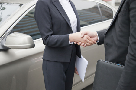 end of a long day: Business People Shaking Hands By Car