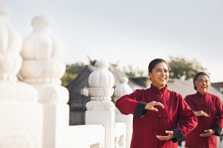 Two seniors practicing Taijiquan in Beijing, arms in a circle photo