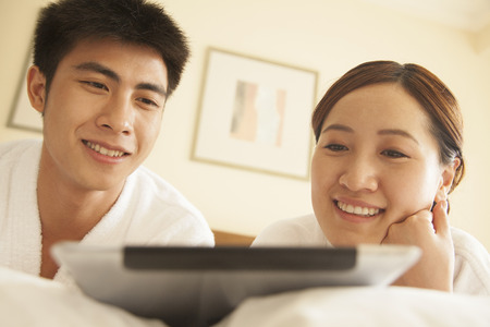 Young Couple Using Tablet in Bed