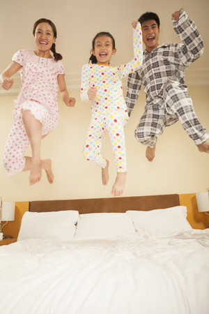 Family Jumping on Bed Together photo