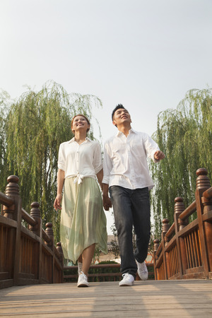 Young Couple Holding Hands and Crossing a Bridge photo