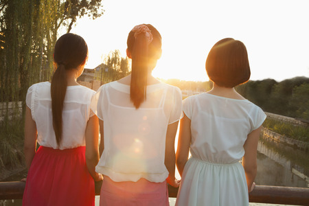 downstream: Three Young Women Looking Downstream at a Sunset