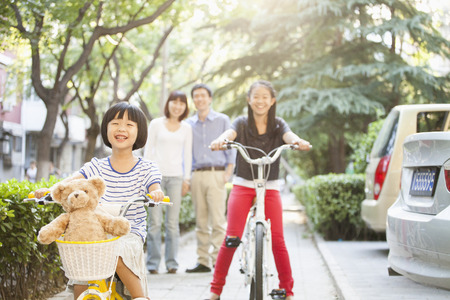men 45 years: Sisters Ride Their Bicycles While Parents Watch