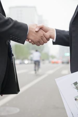 end of a long day: Business People Shaking Hands On Road