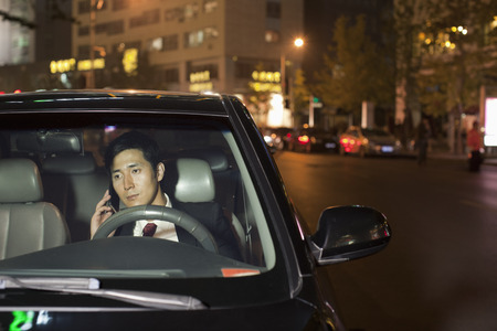 front of: Businessman With Cell Phone In Car Stock Photo
