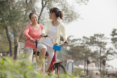 Grandmother and granddaughter riding tandem bicycle, Beijing photo