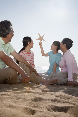 generational: Multi generational family sitting on the beach looking at starfish