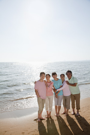 Multi generational family portrait, arms around each other by the beach