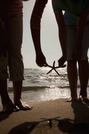 girls at the beach series: Silhouette of mother and daughter picking up a starfish on the beach Stock Photo