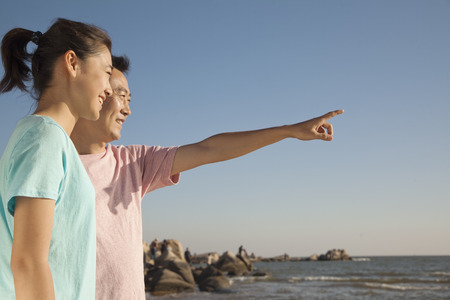 girls at the beach series: Father and Daughter pointing and looking to the sea Stock Photo