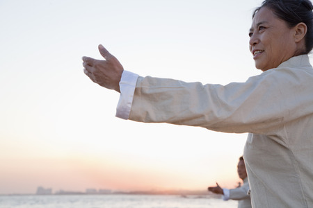 Two older people practicing Taijiquan on the beach at sunset, China