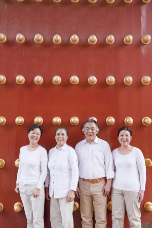 mature people: Group of mature people standing next to traditional Chinese door, portrait