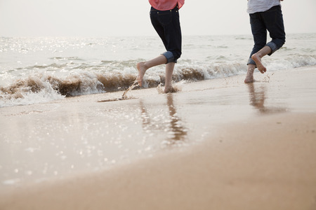 human body part: Young Couple Running in the Waves