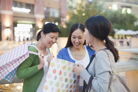 Three Women Looking Into Shopping Bag photo