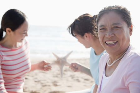 multi generational: Portrait of multi- generational family on the beach, starfish Stock Photo